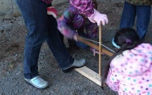 child starting fire with bow drill